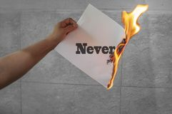 Never word on fire with burning paper. In hand royalty free stock photography