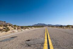 A neverending road to the horizont. A obsolete asphaltic road with orange medial strip going threw a desert in the USA Royalty Free Stock Images