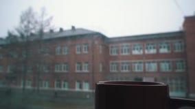 Nevicando fuori della finestra e cuocere a vapore dalla tazza archivi video