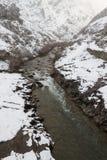 Nevicando nel paesaggio della montagna con il fiume Fotografia Stock Libera da Diritti