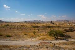 NEVSEHIR-OMRÅDE, CAPPADOCIA, TURKIET: Det härliga höstlandskapet på fält, vaggar och berg På horisonten konturn av royaltyfri fotografi
