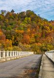 Bridge to Nevytsky Castle hill in autumn. Nevytsky Castle, Ukraine - October 27, 2016: bridge to Nevytsky Castle hill with yellow foliage in autumn forest Royalty Free Stock Images
