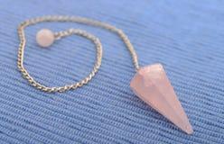 New age crystal pendulum. New age rose quartz crystal pendulum Royalty Free Stock Photos