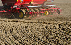 New agriculture cereal grain seeder machinery working on field. New agriculture cereal grain seeder machinery working on farm field. Grain sowing concept Stock Image