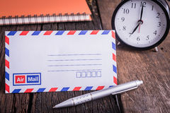 New airmail envelope and ballpoint pen with alarm clock. On old wooden table Stock Photo