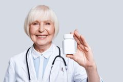New antibiotic. Beautiful senior woman in lab coat holding a bottle with medicines and smiling while standing against grey background royalty free stock images