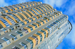 A new apartment building. View angle. New apartment building with yellow balconies against cloudy sky Royalty Free Stock Image