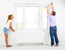 New apartment. Couple is measuring their new empty apartment Royalty Free Stock Photo