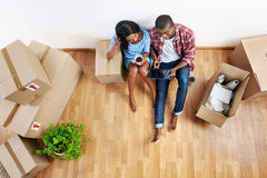 New apartment couple. Overhead view of young black african couple with moving boxes in new apartment using modern tablet computer technology Stock Photos