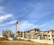 New apartments construction site. Crane over blue sky, building blocks, property half-ready houses, development industry concept. Crane over blue sky, building royalty free stock image