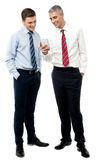 This a new application i have installed. Two male business executives using smart phone royalty free stock image