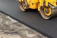 New asphalt road. Road asphalt works. Construction works. Stock Photos
