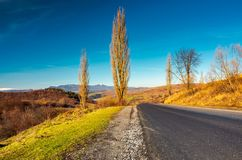 New asphalt road in to the mountains. Pikui mountain with snowy top in the distance. beautiful sunny weather in late autumn. location Volovets serpentine royalty free stock photo