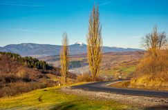 New asphalt road in to the mountains. Pikui mountain with snowy top in the distance. beautiful sunny weather in late autumn. location Volovets serpentine stock images