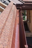 New asphalt shingle roof with brown rain gutter, wooden beams and vapour control layer. Royalty Free Stock Photos