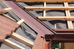 New asphalt shingle roof with brown rain gutter, wooden beams and vapour control layer. Stock Photo