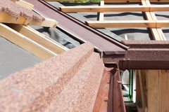New asphalt shingle roof with brown rain gutter, wooden beams and vapour control layer. Stock Images