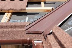 New asphalt shingle roof with brown rain gutter, wooden beams and vapour control layer. New asphalt shingle roof with brown rain gutter, wooden beams and vapour Royalty Free Stock Photos