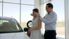 New auto gift for beloved feminine, surprises for girlfriend, Car sales center, Man Standing Behind Woman and Covering. Her Eyes, Man Surprising girl with New stock video footage