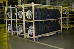 New automobile wheels lie on a rack in assembly shop of automobi Stock Image