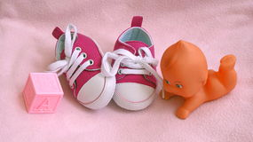 New Baby. A pair of baby's sneakers, building block and baby doll Royalty Free Stock Images