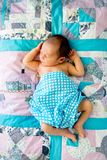 New Baby Boy blue and white checked wrap on pathwork quilt. New Baby Boy sleeping in wrapped in blue and white checked wrap on pathwork quilt with arms and legs Royalty Free Stock Images