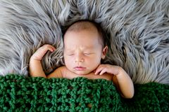 New Baby Boy sleeping covered by dark olive green crotcheted bla. Nket on fluffy grey fur rug, with arms out - caucasian and pacific islander ethnicity Stock Photos