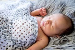 New Baby Boy sleeping covered by grey and white crotcheted blank. Et on fluffy grey fur rug, with arms out - caucasian and pacific islander ethnicity Royalty Free Stock Photos