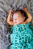 New Baby Boy sleeping covered by light turquoise blue crotcheted. Blanket on fluffy grey fur rug, with arms out - caucasian and pacific islander ethnicity Stock Photo