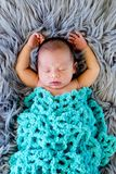 New Baby Boy sleeping covered by light turquoise blue crotcheted. Blanket on fluffy grey fur rug, with arms out - caucasian and pacific islander ethnicity Stock Image