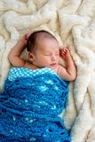 New Baby Boy sleeping wrapped in blue crotchet wool blanket. On cream fur rug with arms out - caucasian and pacific islander ethnicity Royalty Free Stock Photos