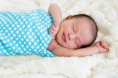 New Baby Boy sleeping wrapped in blue and white checked wrap. On cream fur rug with arms out - caucasian and pacific islander ethnicity Royalty Free Stock Photo