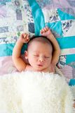 New Baby Boy sleeping wrapped in fluffy cream blanket on pathwor. K quilt with arms out - caucasian and pacific islander ethnicity Stock Photo