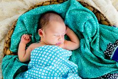 New Baby Boy in woven basket sleeping wrapped in  checked wrap. On green patterned scarf with arms out - caucasian and pacific islander ethnicity Stock Photo