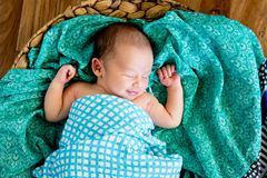 New Baby Boy in woven basket sleeping wrapped in  checked wrap. On green patterned scarf with arms out - caucasian and pacific islander ethnicity Stock Photos