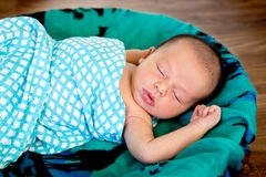 New Baby Boy in woven basket sleeping wrapped in  checked wrap. On green patterned scarf with arms out - caucasian and pacific islander ethnicity Royalty Free Stock Photos