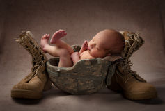 Newborn in Military Helmet. New baby in his father's army helmet with boots