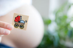 A new baby. A pregnant woman holding a memory card with a baby buggy on it Royalty Free Stock Image