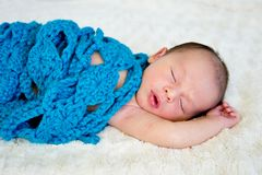 New Baby sleeping wrapped in blue crotchet wool blanket. On cream fur rug with arms out - caucasian and pacific islander ethnicity Royalty Free Stock Photography