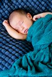 New Baby sleeping wrapped in green wool blanket on dark blue tex. Tured blanket with arms out - caucasian and pacific islander ethnicity Stock Photos