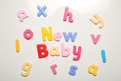 New baby spelt in magnet letters. On a plain white background Royalty Free Stock Photos