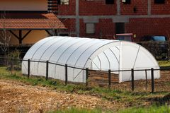 New backyard garden greenhouse made of metal pipes and white opaque nylon placed in local garden behind family house surrounded. With dry soil and houses on royalty free stock image