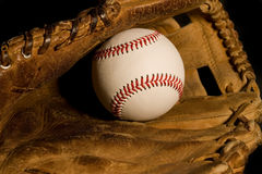 New baseball Old glove. New baseball resting in old worn glove Stock Photo