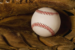 New Baseball Old Glove. New baseball laying in old worn glove Stock Images