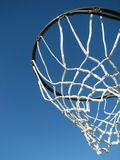 New basketball hoop waiting for a game to start. Shot of a basketball rim and net taken against the deep blue sky from below stock image