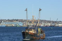 Fishing trawler Hustler with waterfront background. New Bedford, Massachusetts, USA - March 31, 2018: Fishing trawler Hustler leaving New Bedford harbor Royalty Free Stock Image