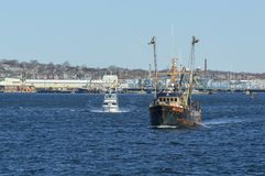 Yacht and fishing boat leaving New Bedford. New Bedford, Massachusetts, USA - March 31, 2018: Yacht Chill-N following fishing vessel Hustler out of New Bedford Stock Images