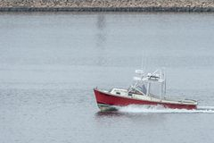 Powerboat Pal Dao leaving New Bedford. New Bedford, Massachusetts, USA - May 7, 2018: Powerboat Pal Dao heading for Buzzards Bay with hurricane barrier in Royalty Free Stock Photo