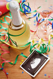 New beginning , new year , new life. The bottle of champagne and ultrasound photo of baby royalty free stock photos