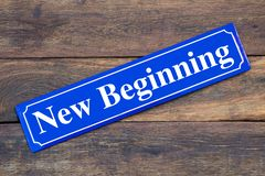 New Beginning street sign on wooden background. As symbol stock photography